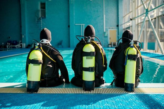 강사와 정장을 입은 두 명의 다이버가 수영장 옆, 뒷모습, 다이빙 학교에 앉아 있습니다. 사람들에게 스쿠버 장비로 수중 수영을 가르치고, 배경에 실내 수영장 내부, 그룹 훈련