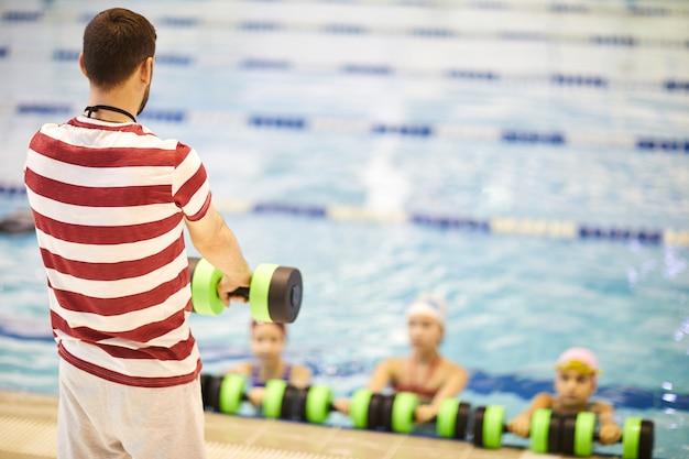 Инструктор проводит занятия по аквааэробике