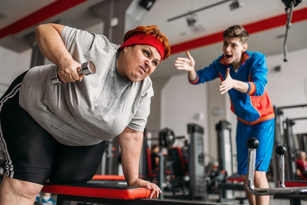 Instructor forces fat woman to exercise with dumbbells in gym.