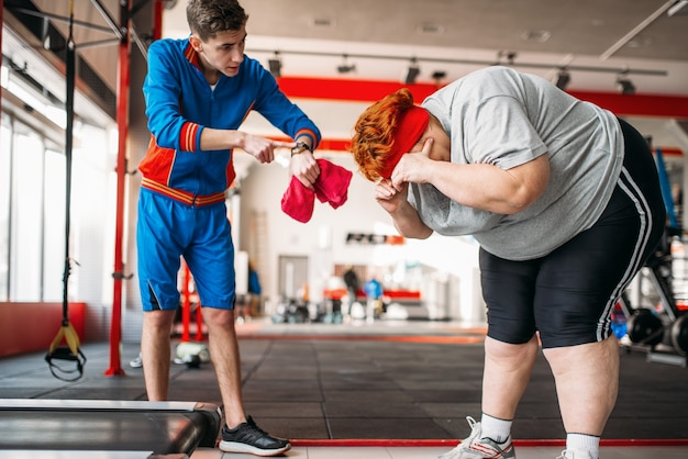 Инструктор заставляет толстую женщину выполнять упражнения, тяжелые тренировки в тренажерном зале.