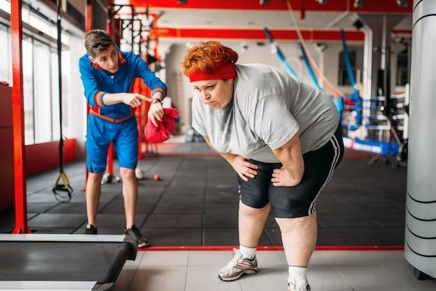 Инструктор заставляет толстую женщину заниматься в тренажерном зале