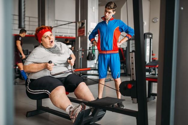 강사는 뚱뚱한 여자가 운동 기계, 체육관에서 열심히 운동하도록 강요합니다.