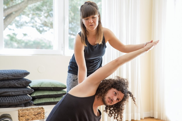Instructor helping man to do side bend at yoga class