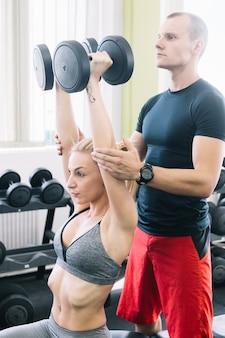Инструктор, помогающий женщине в тренажерном зале