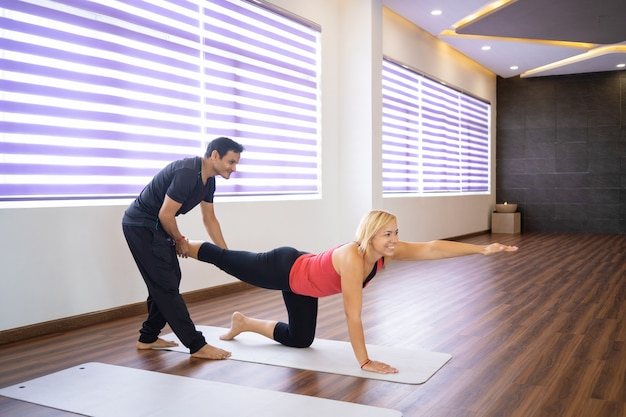 Instructor helping woman to do bird dog pose at yoga class