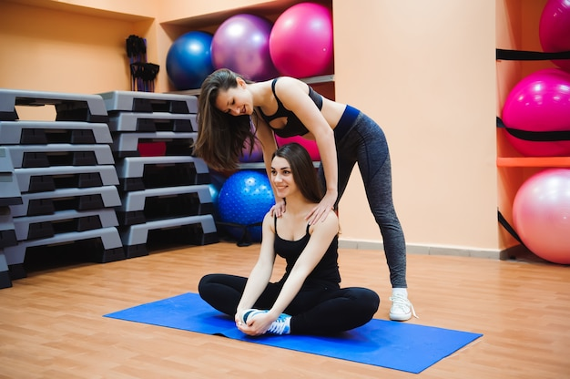 Instructor helping young girl doing stretching. women doing stretching.
