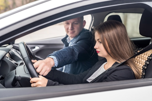 Instructor helping young woman drive a car
