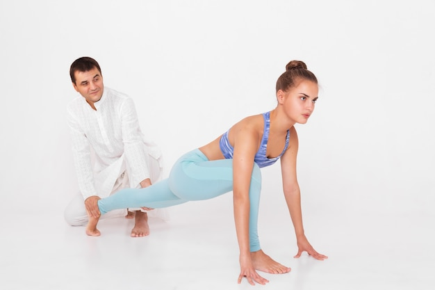 Instructor helps beginner to make asana exercises.