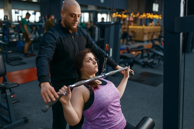 インストラクターは、エクササイズマシン、ジムで女性を太りすぎにするのに役立ちます