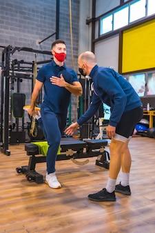 코로나 바이러스 전염병에서 젊은 운동 선수의 운동을 교정하는 체육관의 강사