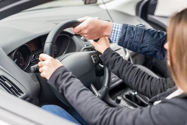 여성에게 운전을 돕는 강사의 손
