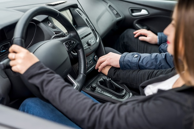 젊은 여자가 차를 운전하는 것을 돕는 강사의 손