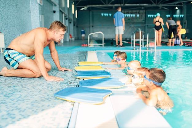 수영장에서 아이들과 이야기하는 강사
