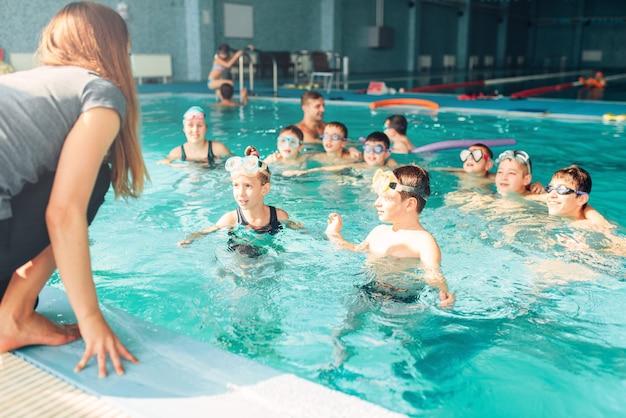강사가 아이들에게 수영 방법을 가르칩니다.