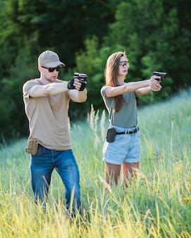 The instructor teaches the girl to shoot a pistol at the range