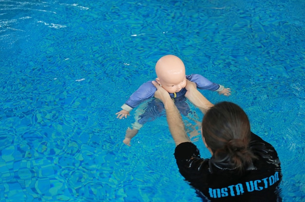 Instructor training dummy drowning baby doll in the pool.