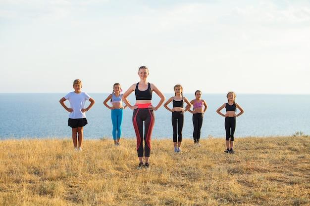 Инструктор обучает детей йоге в горах на берегу океана.