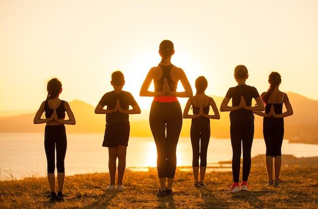 강사는 바다의 산에서 요가 어린이를 훈련시킵니다.