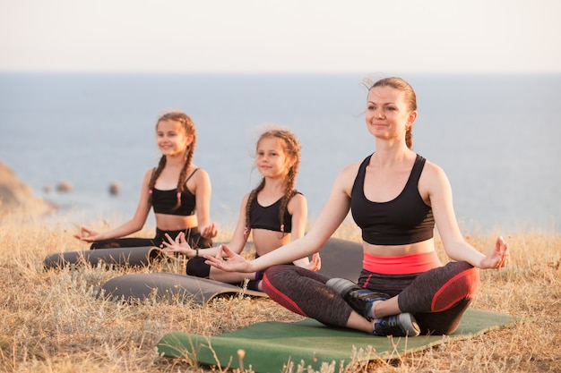 Instructor trains yoga kids in the mountains on the ocean.