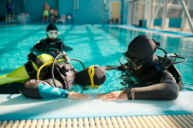 Instructor and two divers in aqualungs, course in diving school. teaching people to swim underwater with scuba gear, indoor swimming pool interior on background, group training