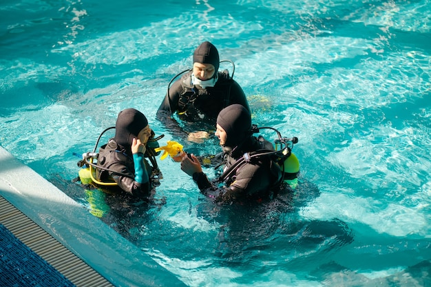 Instructor and two divers in aqualungs, dive course in diving school. teaching people to swim underwater with scuba gear, indoor swimming pool interior on background, group training