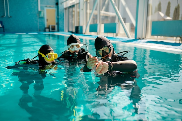 Instructor and two divers in aqualungs, dive lesson in diving school. teaching people to swim underwater with scuba gear, indoor swimming pool interior on background, group training