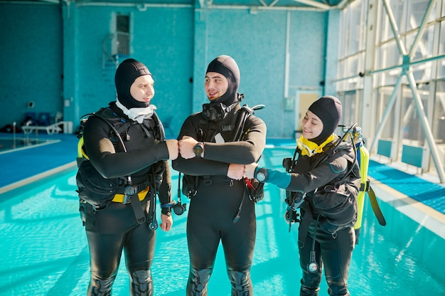 Instructor and two divers in suits, diving school. teaching people to swim underwater with scuba gear, indoor swimming pool interior on background, group training