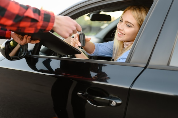 Instructor with checklist gives the keys to student in car, examination or lesson in driving school