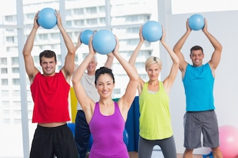 Instructor with class exercising with fitness balls