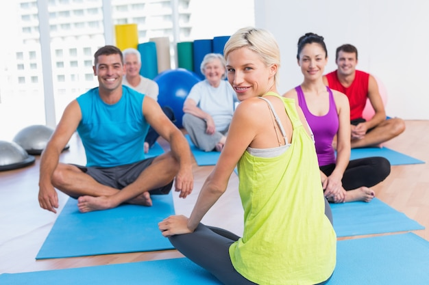 Instructor with class practicing yoga in fitness studio