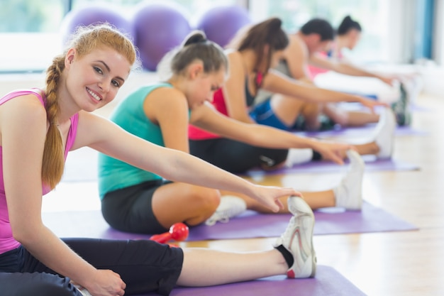 Instructor with class stretching legs in exercise room