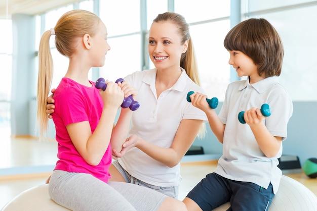子供とインストラクター。ヘルスクラブでの運動で子供たちを助ける陽気なインストラクター