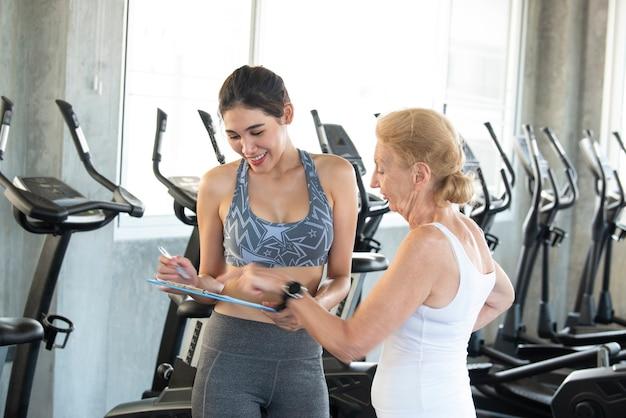 リハビリテーションセンターの年配の女性とインストラクター。ドキュメントクリップボードに何かを表示するパーソナルトレーナー。