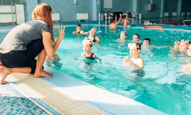 강사는 수영장에서 아이들과 함께 일합니다
