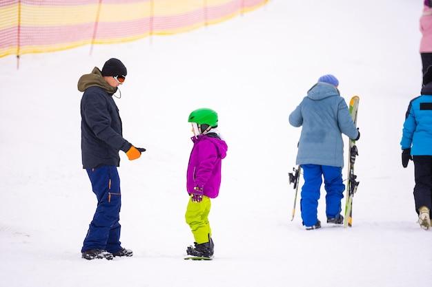 Инструкторы учат ребенка на снежном спуске кататься на сноуборде