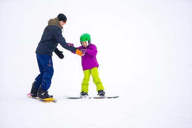 インストラクターは、スノースロープで子供にスノーボードを教える