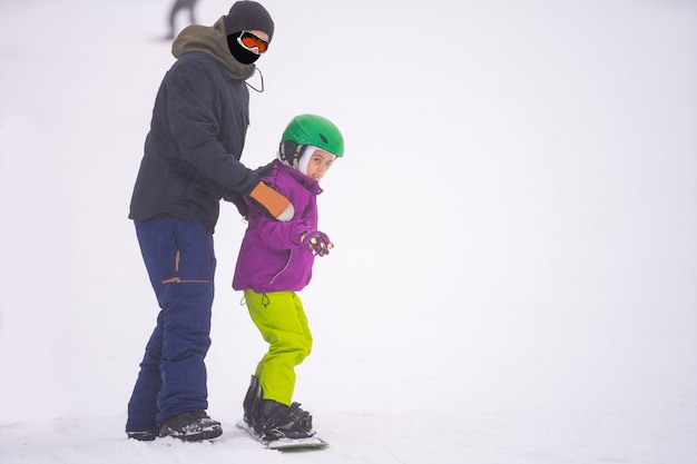 Instructors teach a child on a snow slope to snowboard