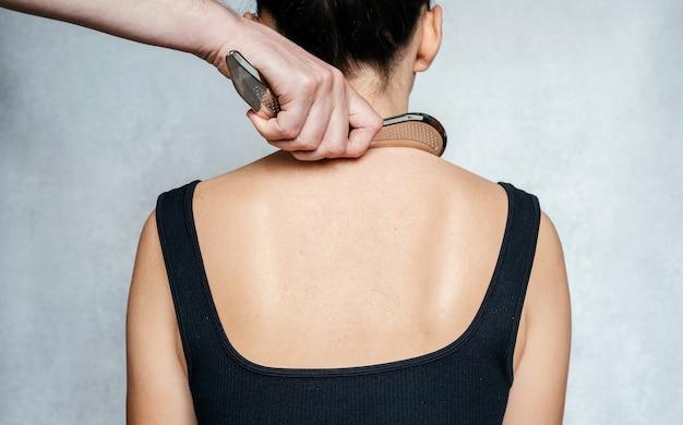 Инструментальная мобилизация мягких тканей, женщина, получающая лечение мягких тканей спины с помощью инструмента из нержавеющей стали iastm