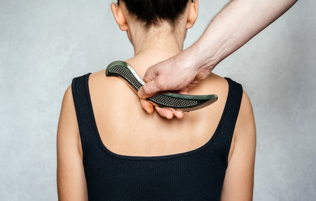 Instrument-assisted soft tissue mobilization, a woman receiving soft tissue treatment on her back with iastm stainless steel tool