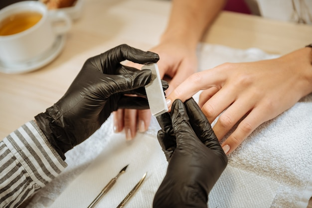 マニキュア用器具。マニキュア用の楽器を使用して黒い手袋を着用した経験豊富なネイリスト