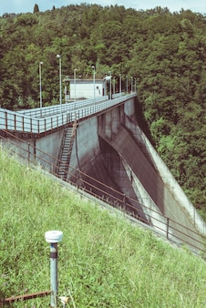 Instruments of measurement (strain gauge and topographic level) for stability monitoring on a dam.