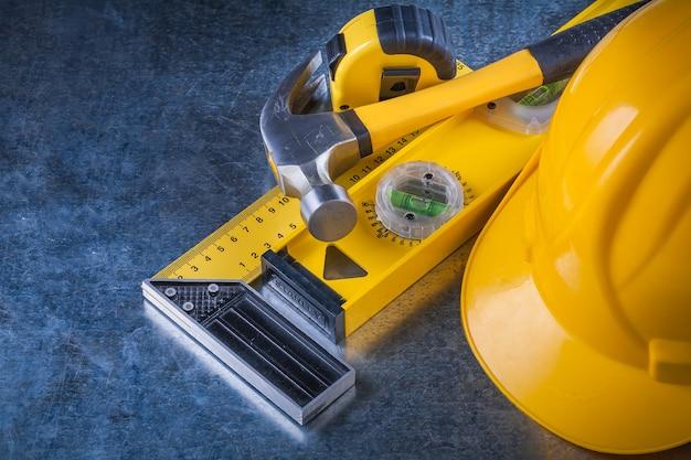 引っかき傷のある金属製の背景のメンテナンスコンセプトに基づいた測定用クローハンマーとヘルメットの構築。
