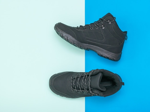 Insulated black casual men's shoes on blue and blue background. men's shoes for cold weather. flat lay.