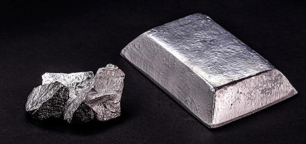 절연 검정색 배경의 아연 덩어리 옆에 절연 아연 잉곳 또는 막대, 합금 및 강철 생산에 사용되는 금속