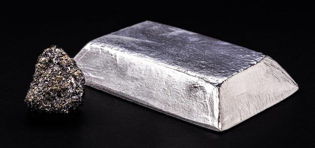 Изолированный цинковый слиток или стержень рядом с самородком цинка на изолированном черном фоне, металл, используемый в производстве сплавов и стали