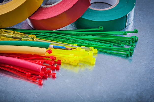 Insulating tapes plastic cable ties electric wires on metallic table