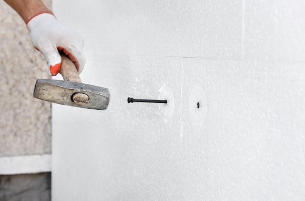 Утепление дома пенопластом. рабочий использует молоток для дюбелей, которыми крепятся полистирольные плиты.