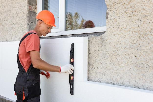 발포체로 집을 단열합니다. 작업자는 건축 수준과 함께 외관에 폴리스티렌 보드 설치의 정확성을 확인하고 있습니다.