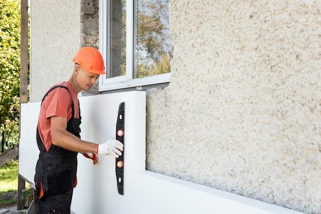 ポリフォームによる家の断熱。作業員は、ファサードへのポリスチレンボードの取り付けの正確さを建設レベルで確認しています。