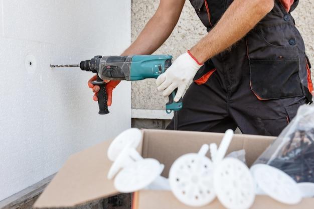 Утепление дома пенопластом. рабочий сверлит отверстия для крепления пенополистирола на фасаде.